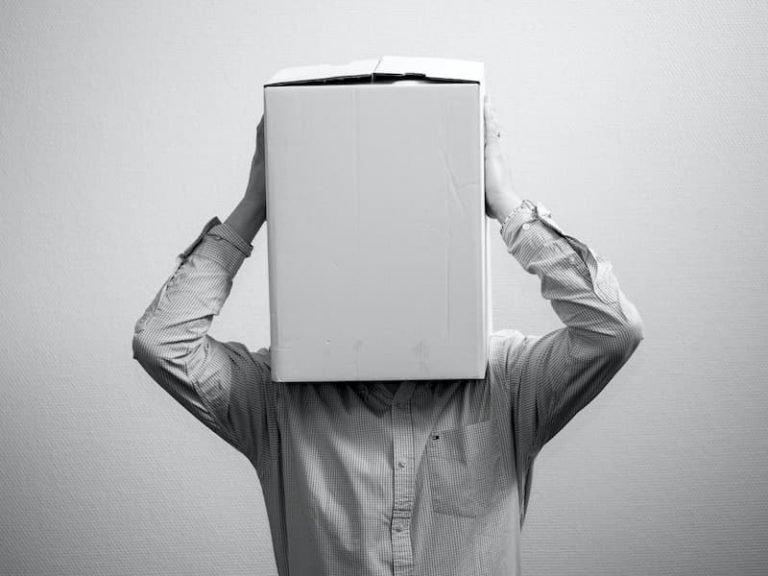 La crisis del éxito, hombre con una caja de carton en la cabeza